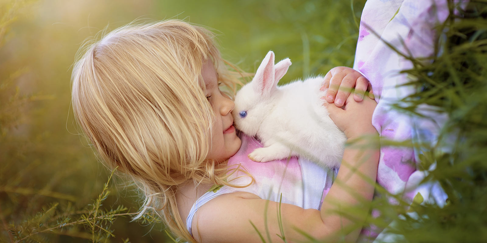 Little girl cradling pet rabbit.