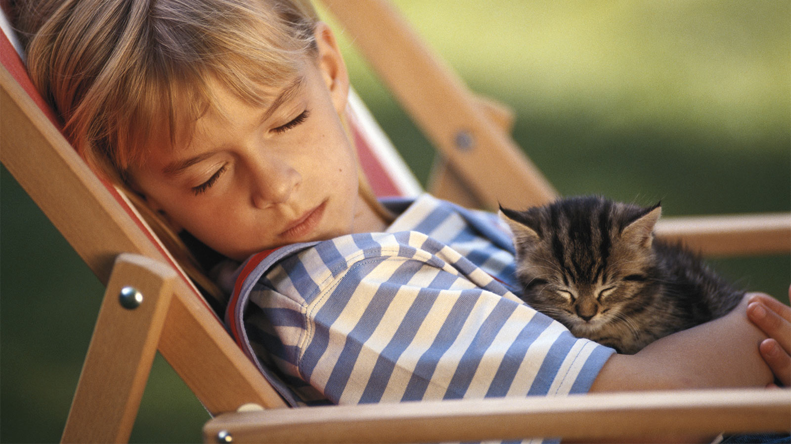 Girl napping on a lawn chair with her kitten.
